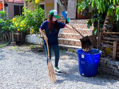 พนักงานเอ.เบสท์นำเศษขยะจากที่ตักผงใส่ลงในถังขยะสีน้ำ