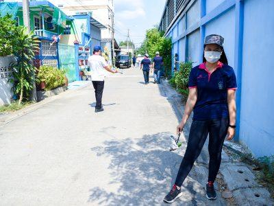 พนักงานเอ.เบสท์ยืนถือที่คีบขยะที่มีขยะอยู่ในที่คีบริมกำแพงสีฟ้า