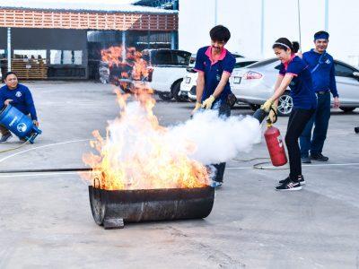 พนักงานชายและหญิงโรงงานบรรจุภัณฑ์เครื่องสำอางช่วยกันดับเพลิงในการอบรม