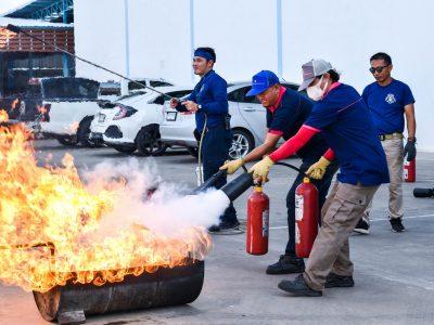 พนักงานชายสองคนโรงงานบรรจุภัณฑ์เครื่องสำอางช่วยกันดับเพลิงในการอบรม