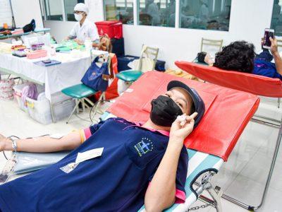 พนักงานผู้หญิงของบริษัทเอ.เบสท์บริจาคเลือดชุสองนิ้วยิ้มแย้ม ใส่หมวกเก็บผมของบริษัท