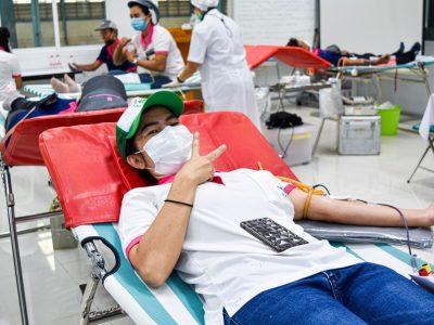 พนักงานผู้หญิงเสื้อสีขาวหมวกสีเขียว บริจาคเลือดกับสภากาชาดไทย