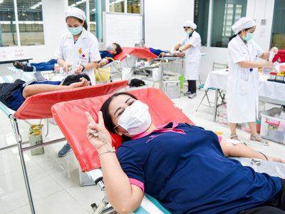 พนักงานผู้หญิงของบริษัทเอ.เบสท์บริจาคเลือดให้แก่สภากาชาดโดยชูสองนิ้วยิ้มแย้ม