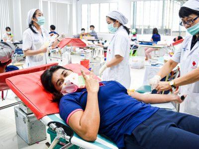 พนักงานผู้หญิงของโรงงานผู้ผลิตและจัดจำหน่ายบรรจุภัณฑ์เครื่องสำอางได้บริจาคเลือด ชูสองนิ้วด้วยใบหน้ายิ้มแย้ม